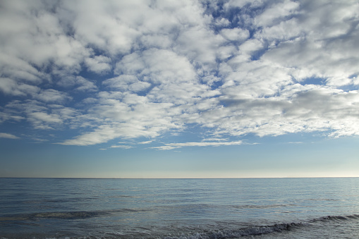 Stratocumulus clouds over blue sea water waves