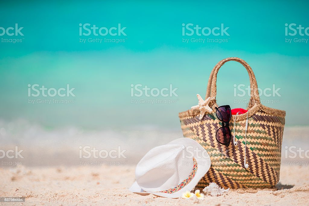 Straw bag, fist star, headphones, hat and sunglasses on white stock photo
