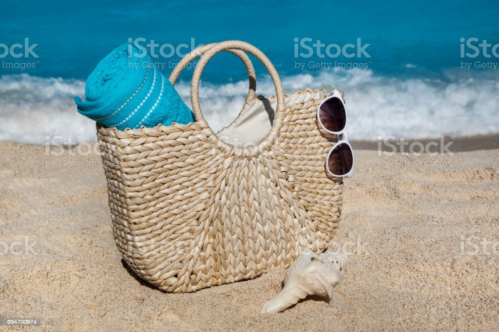 Straw bag with blue towel and sunglasses on tropical sand beach in Cancun, Mexico stock photo