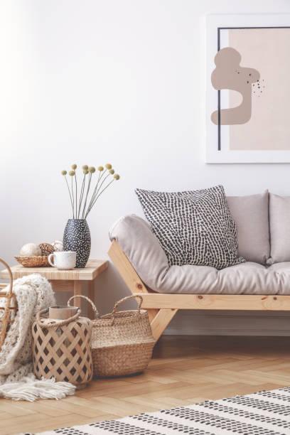 Strohkorb neben komfortablem Sofa und Tisch im eleganten Wohnzimmer-Interieur, echtes Foto – Foto