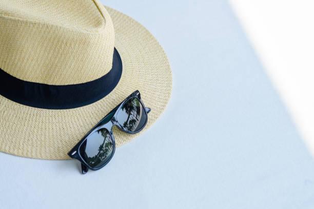 Stroh-Strandmütze mit schwarzem Band und Sonnenbrille auf dem weißen Tisch mit freiem Platz, Reise-Sommer-Konzept – Foto