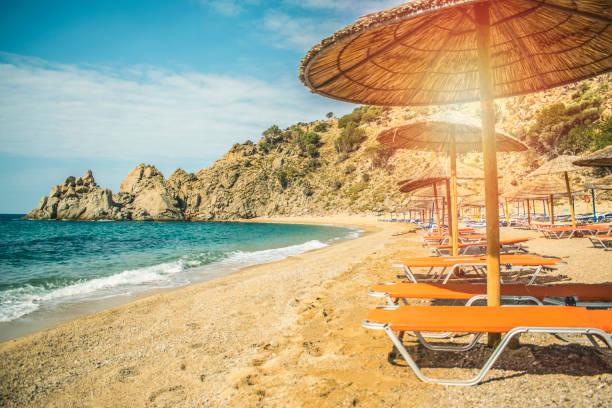 stroh sonnenschirm mit meer ozeanstrand - urlaub in tunesien stock-fotos und bilder
