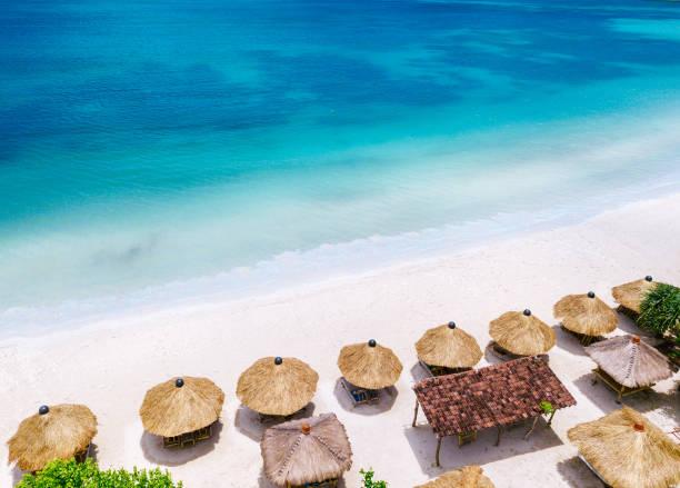 stro parasols en blauwe oceaan. strand scène van bovenaf - bali stockfoto's en -beelden
