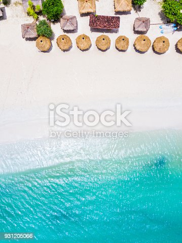 931756010 istock photo Straw beach umbrellas and blue ocean. Beach scene from above 931205066
