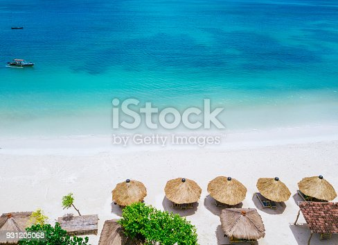 931756010 istock photo Straw beach umbrellas and blue ocean. Beach scene from above 931205068