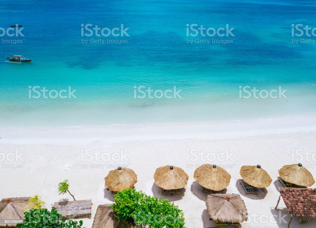 Straw beach umbrellas and blue ocean. Beach scene from above stock photo