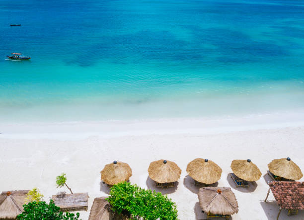stro parasols en blauwe oceaan. strand scène van bovenaf - lombok stockfoto's en -beelden