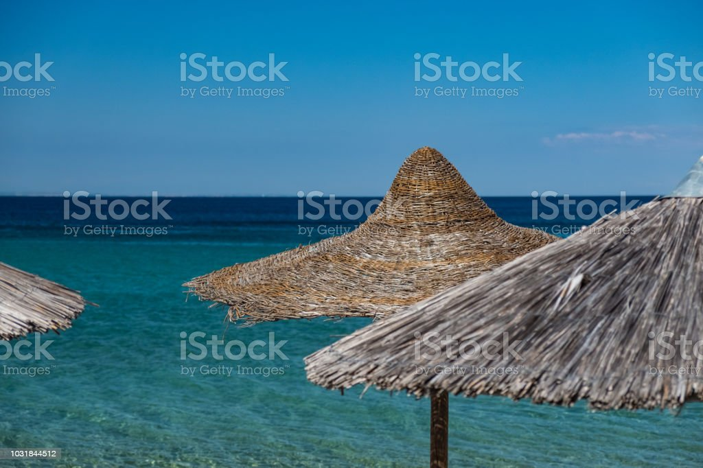 Straw covered umbrella on the beach stock photo
