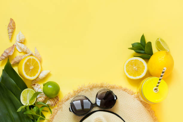 Straw foman's hat, sun glasses and beach accessory with detox citrics water on yellow. Top view. Flat lay. Copy space. Straw foman's hat, sun glasses and beach accessory with detox citrics water on yellow. Top view. Flat lay. Space for text. lemon fruit stock pictures, royalty-free photos & images