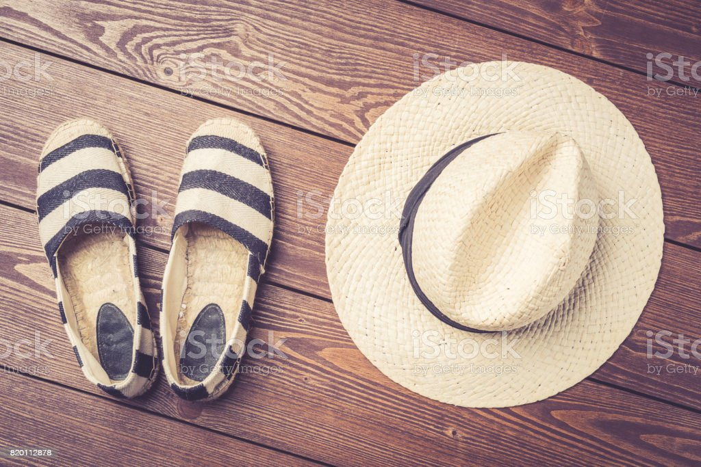 Straw hat and espadrilles on wooden background. stock photo