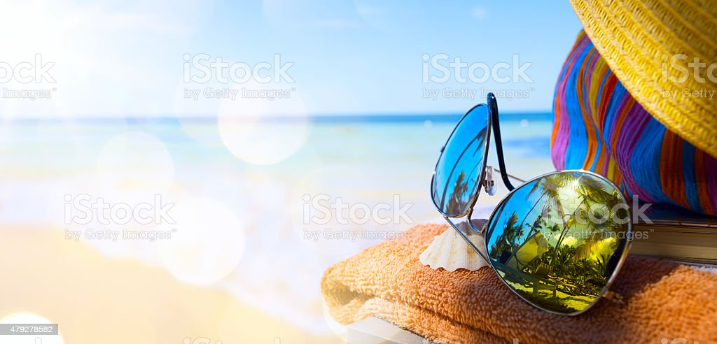 Straw hat, bag and sun glasses  on a tropical beach stock photo