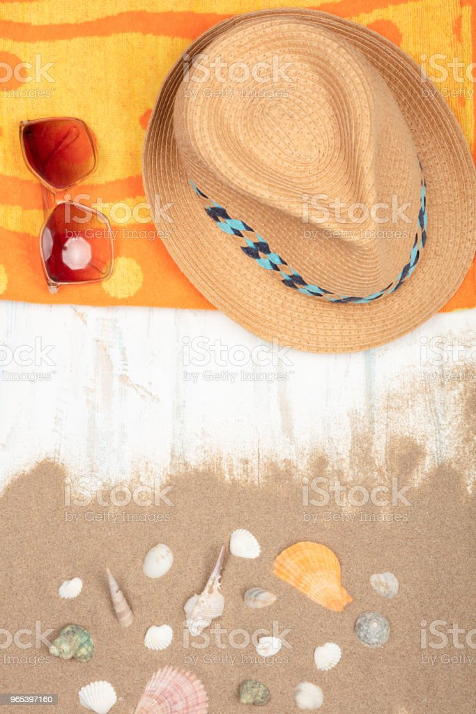 Straw hat ,sunglasses , beach towel with sea shells on sandy  wooden surface royalty-free stock photo