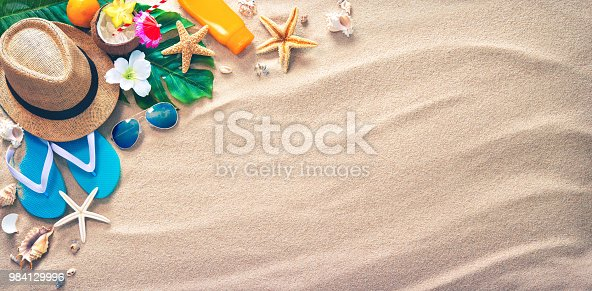 Straw hat with a exotic cocktail and sunglasses on sand beach. Summer Holidays concept