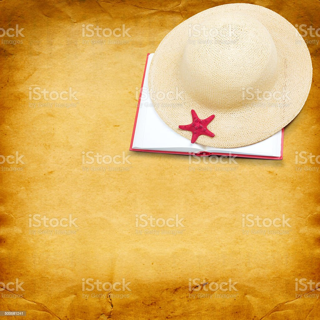 Straw hat with book and red starfish on paper background royalty-free stock photo