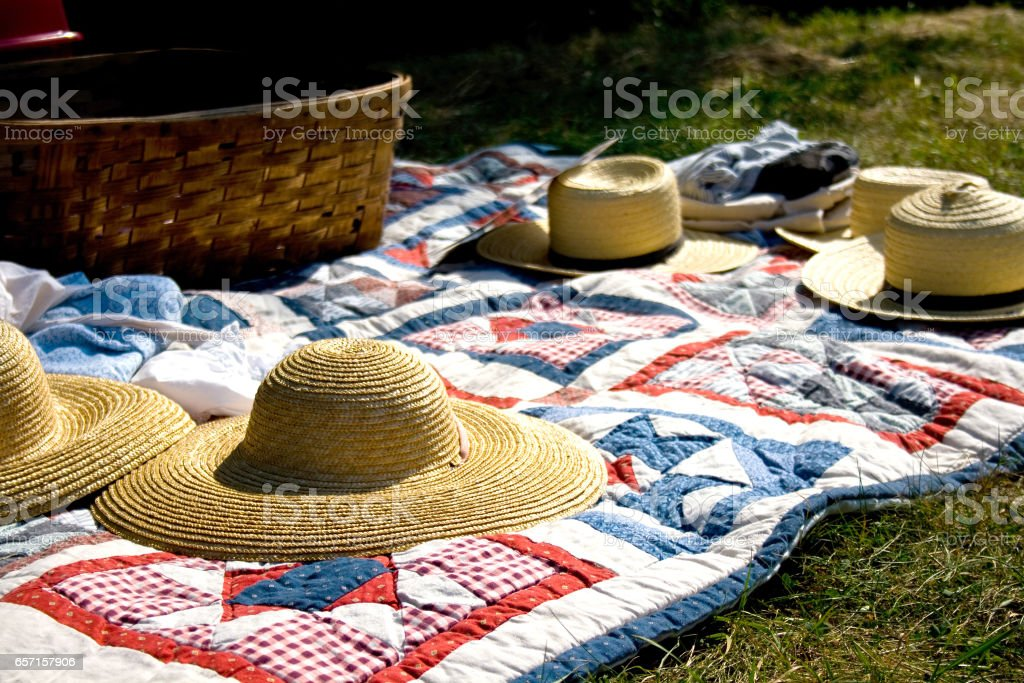 Straw Hats and Picnic Basket on Quilt stock photo