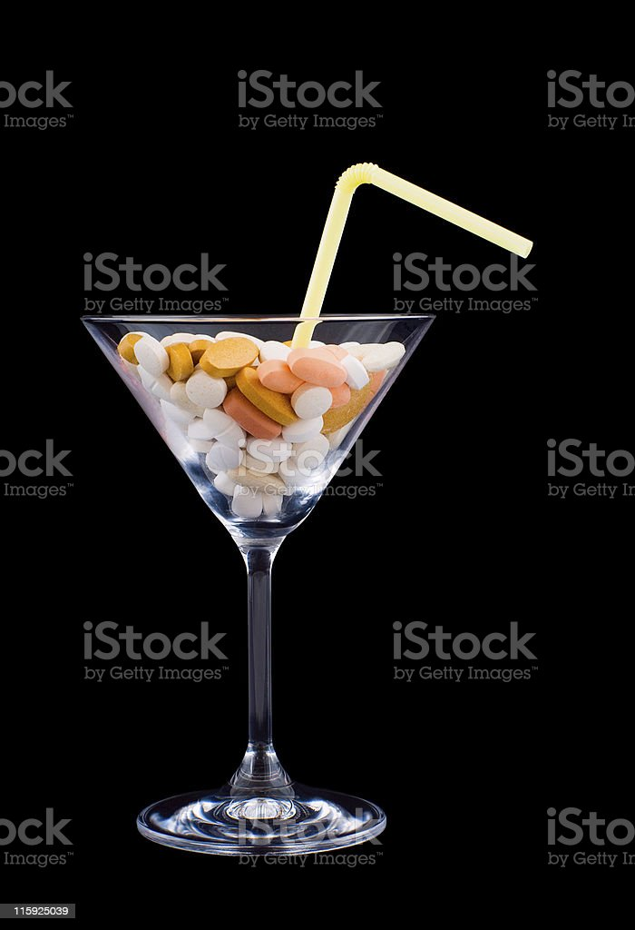Straw in cocktail glass filled with mixture of dangerous pills royalty-free stock photo