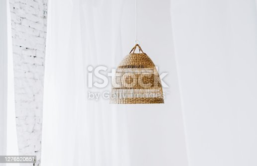 Straw lampshade in bedroom. Eco-friendly design details of bedroom using natural materials. High quality photo