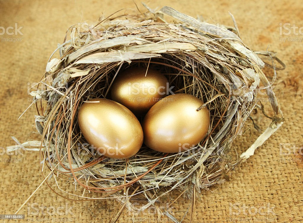 Straw nest with 3 golden eggs inside stock photo