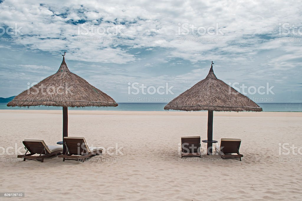 Straw parasols in the beach stock photo