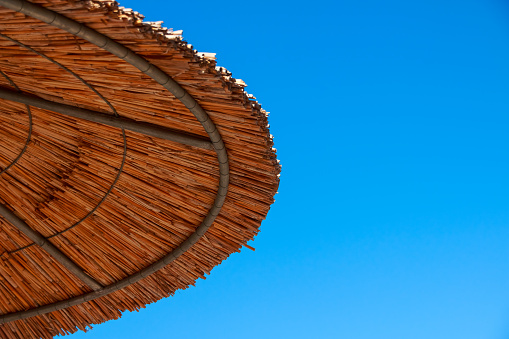 Straw roof of sun umbrella against the blue sky. Vacation topic.summer beach, background for an inscription.Texture of beautiful straw natural sun umbrellas made from hay in a tropical desert resort,