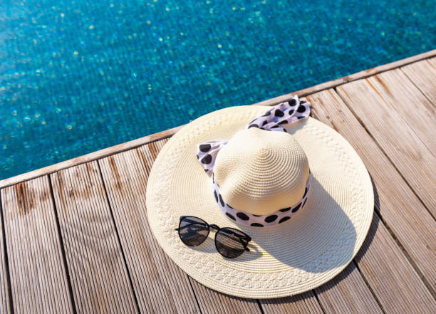 Straw sun hat and sunglasses on the terrace of swimming pool Straw sun hat and sunglasses on the terrace of swimming pool. poolside stock pictures, royalty-free photos & images