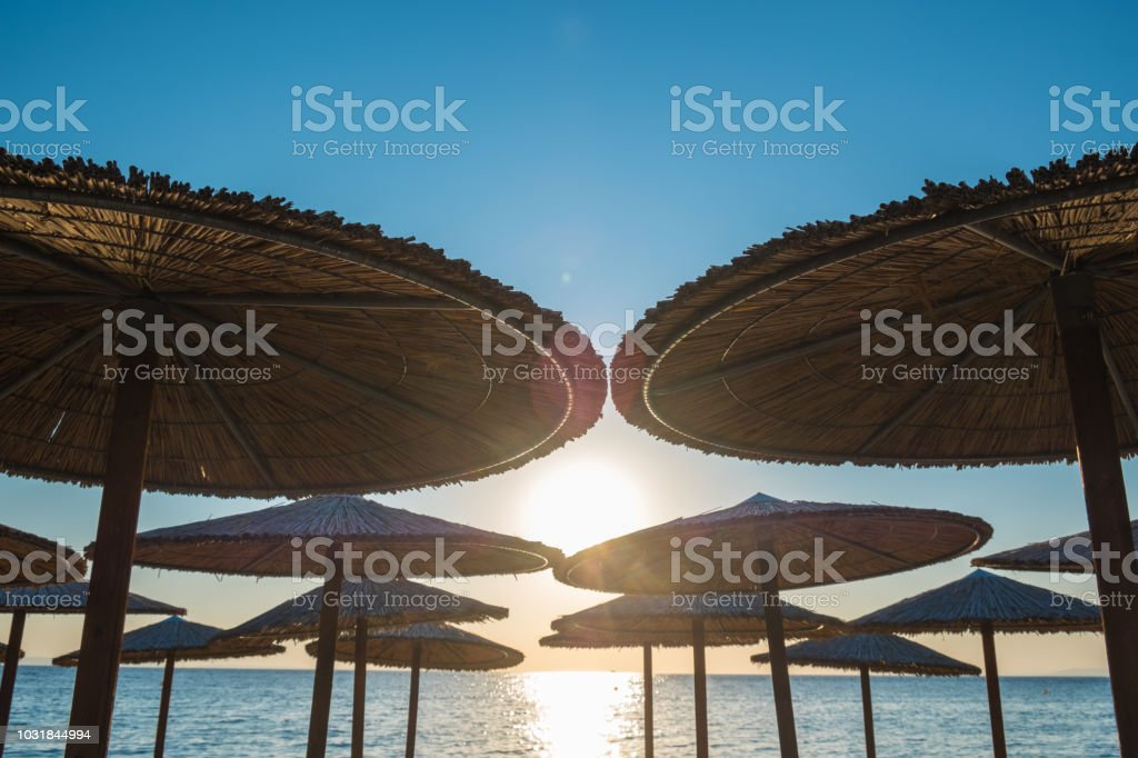 Straw sun umbrellas at the beach stock photo