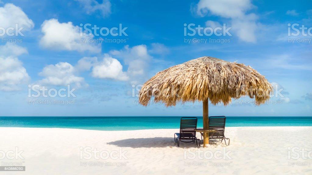 Straw umbrella on Eagle Beach, Aruba stock photo