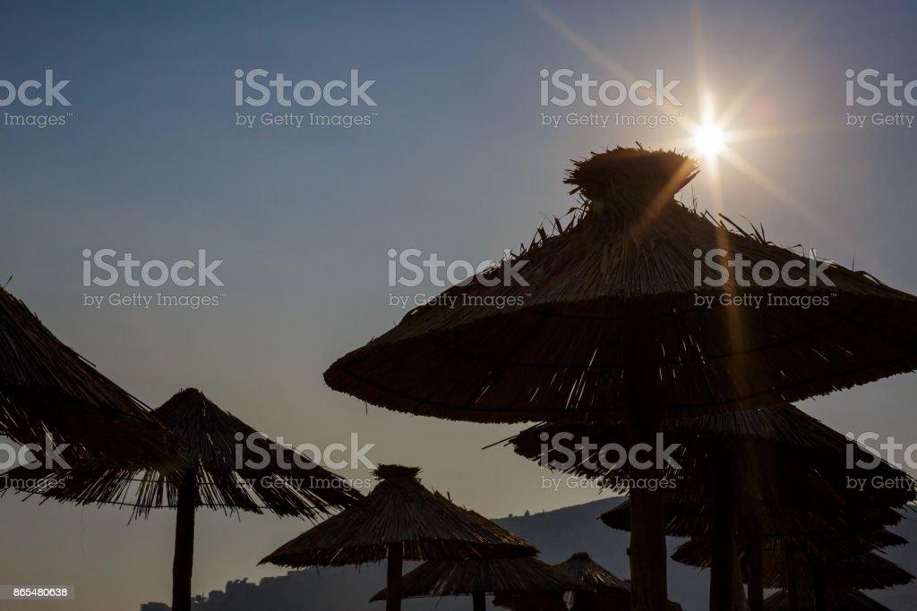 straw umbrellas  against sun stock photo