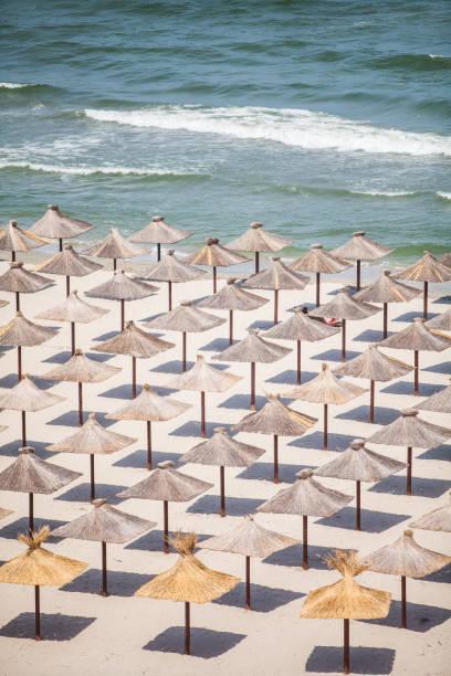 Straw umbrellas on a beach stock photo
