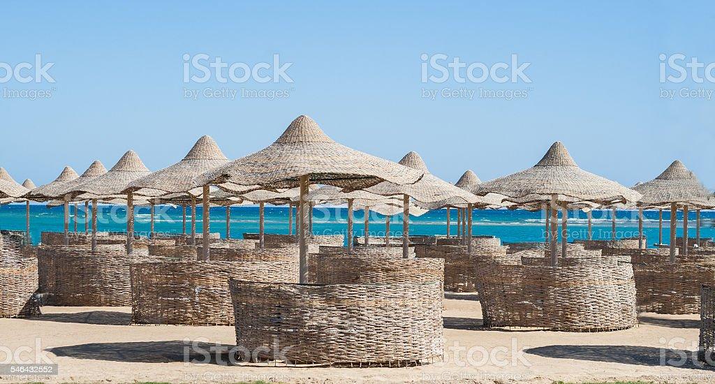 Straw umbrellas on the beach stock photo