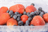 Strawberries and blueberries close-up. Delicious vitamins. Useful fresh berries. Unusual background.