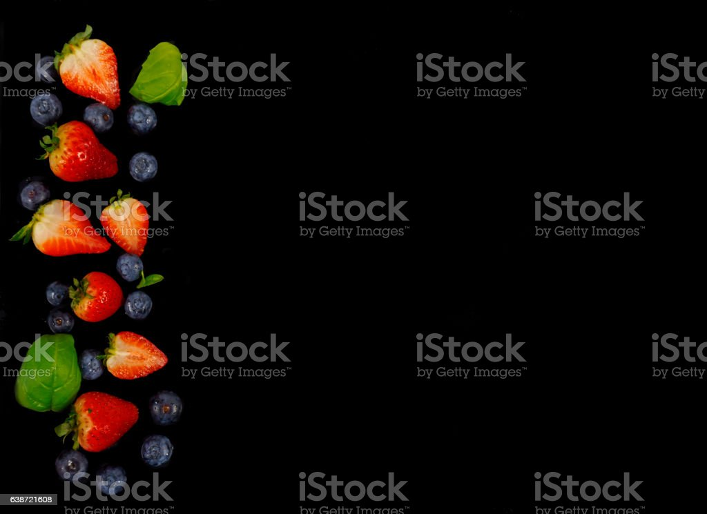 Strawberries and blueberries on a black background stock photo