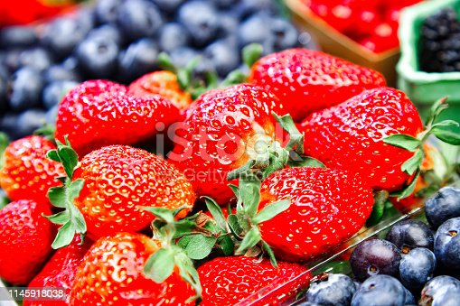 610771802 istock photo Strawberries and different fruits on the background 1145918038