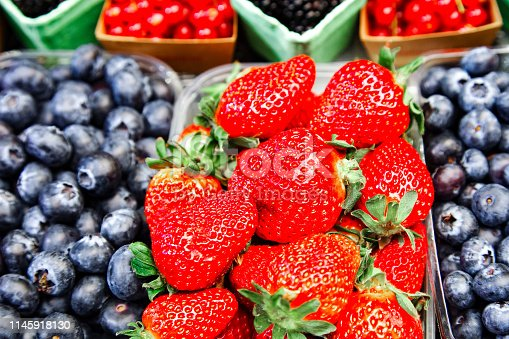 610771802 istock photo Strawberries and different fruits on the background 1145918130