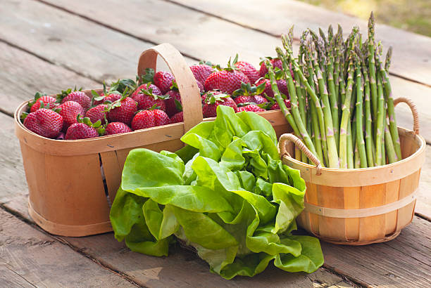"""Strawberries Asparagus and Lettuce """"Crunchy fresh green asparagus, buttery tasting boston lettuce and a  of lucious red strawberries picked in spring fill baskets placed on rough wood outdoors."""" butterhead lettuce stock pictures, royalty-free photos & images"""