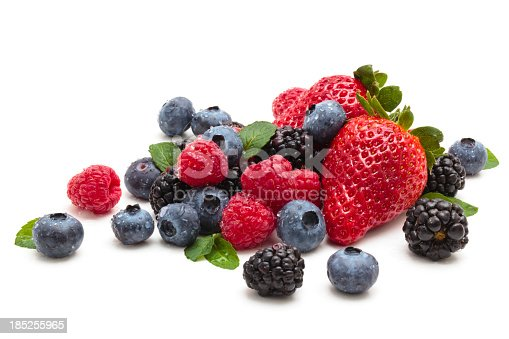 Mix of differrerent berries with leaves. Isolated on white.