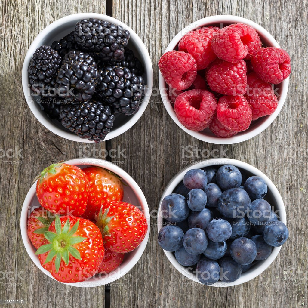 strawberries, blueberries, blackberries and raspberries in bowls stock photo