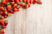 Strawberries copy space with strawberries in the upper left corner scattered on a wooden background taken from above