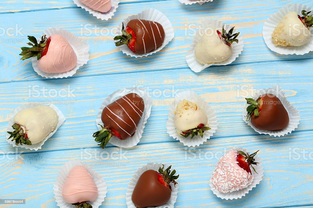 Strawberries covered in chocolate on a blue wooden table stock photo