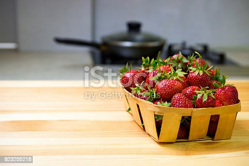 istock Strawberries in a basket on a wooden table. Kitchen. 923255218