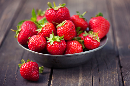 Strawberries in a bowl on rustic wood