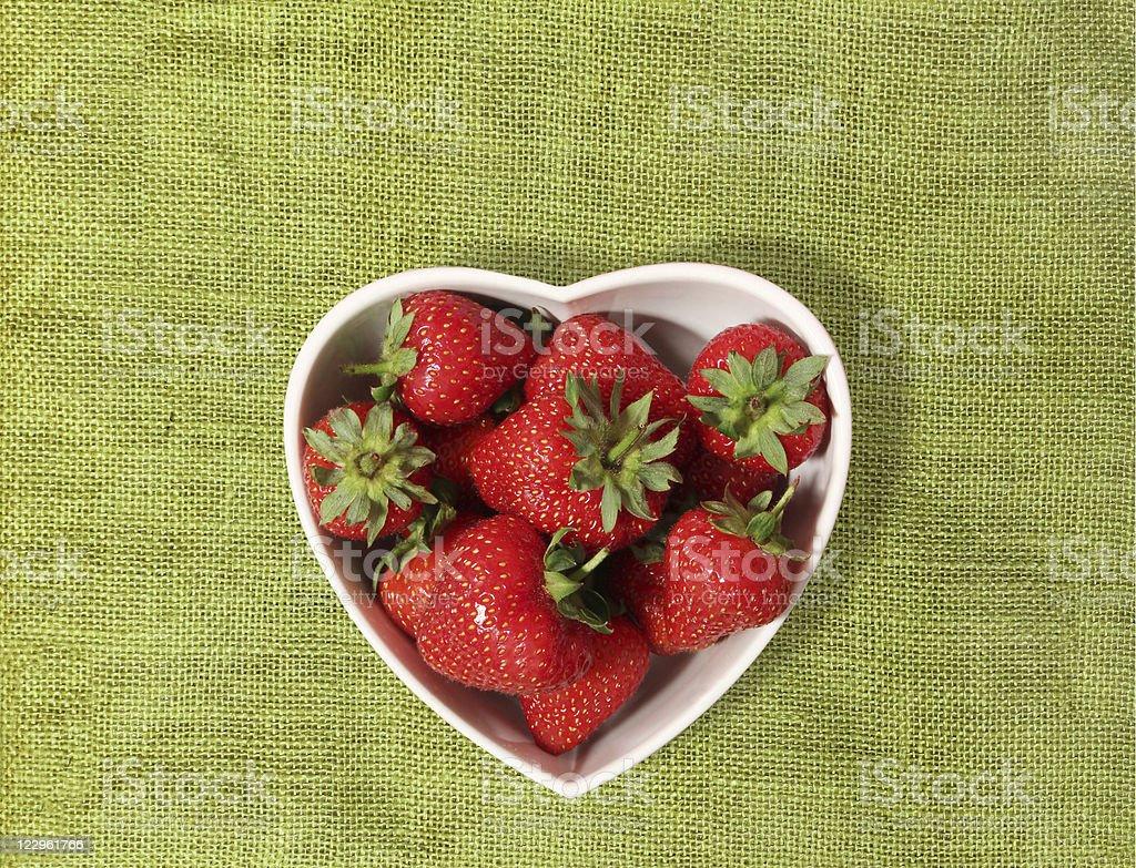Fresas en un tazón de forma de corazón - foto de stock