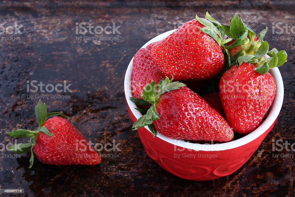 Strawberries in red bowl stock photo