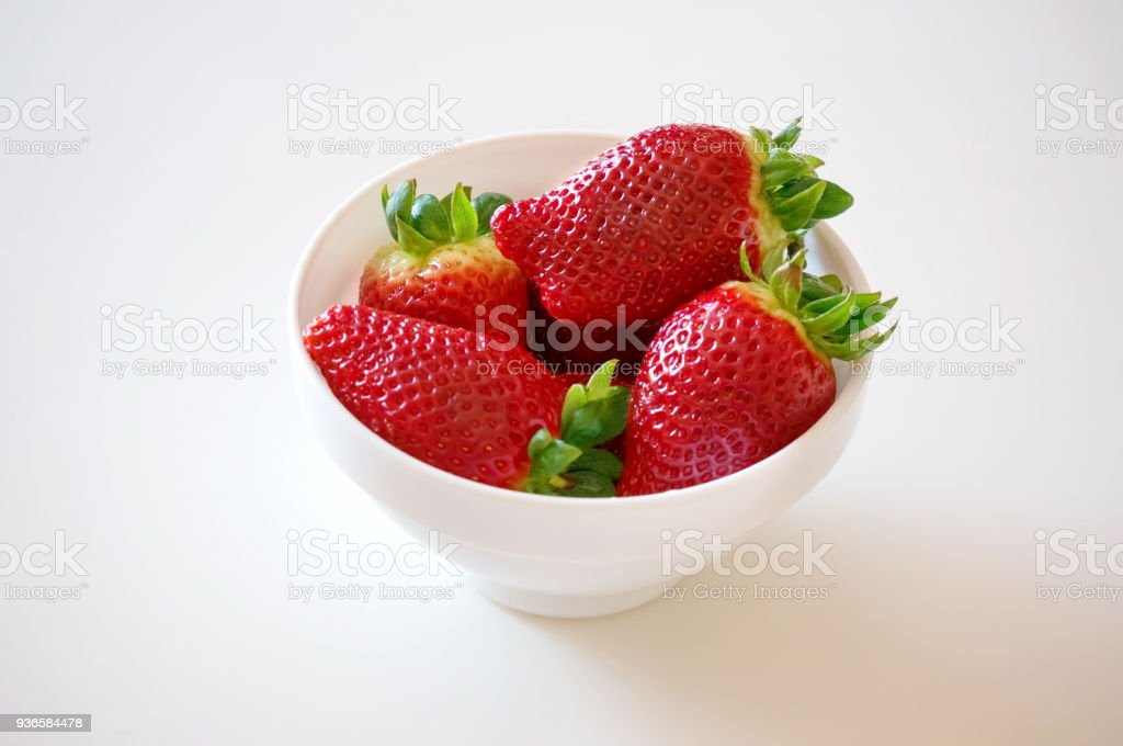 Strawberries lie in a white bowl on a white surface. stock photo