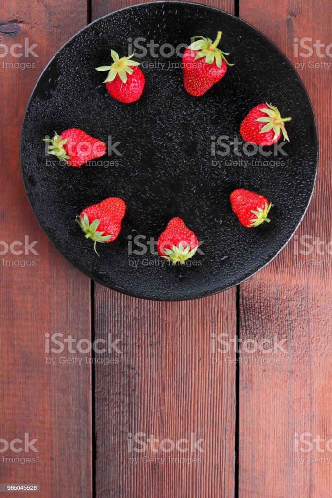 Strawberries on a black plate top view, red berries on a wooden background, fresh strawberries on dark wooden boards, vegetarian food zbiór zdjęć royalty-free