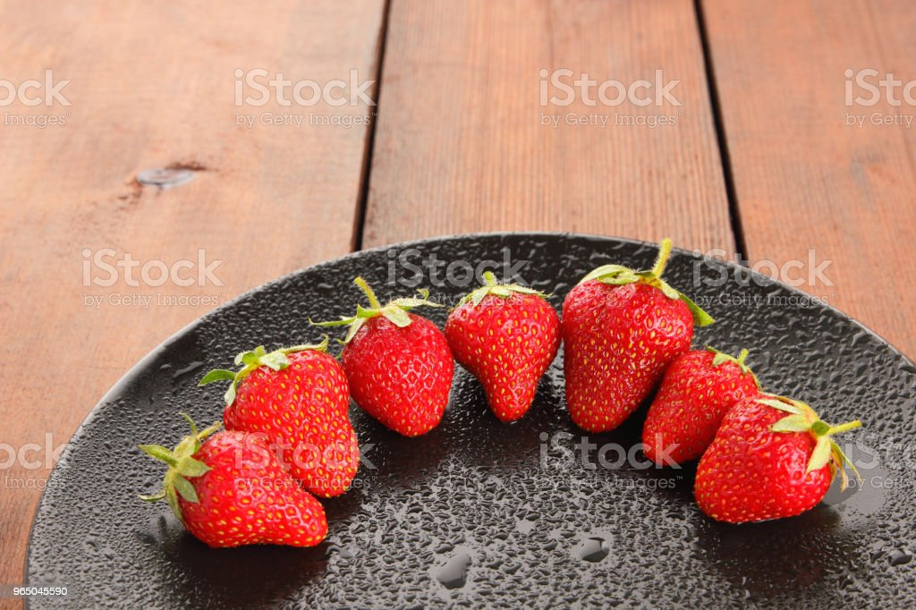 Strawberries on a black plate top view, red berries on a wooden background, fresh strawberries on dark wooden boards, vegetarian food zbiór zdjęć royalty-free