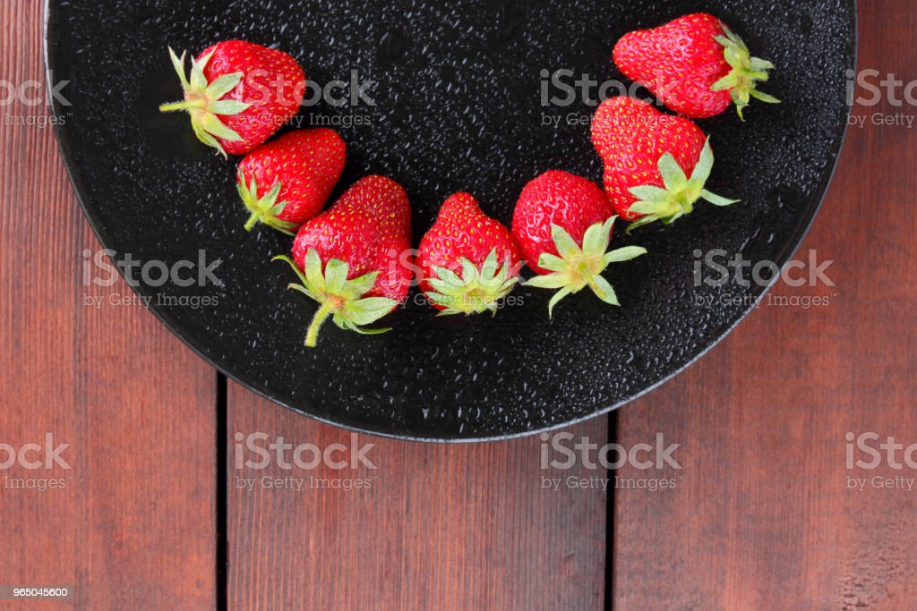 Strawberries on a black plate top view, red berries on a wooden background, fresh strawberries on dark wooden boards, vegetarian food royalty-free stock photo