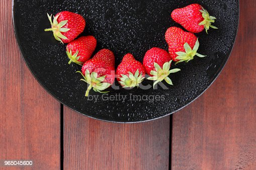 Strawberries On A Black Plate Top View Red Berries On A Wooden Background Fresh Strawberries On Dark Wooden Boards Vegetarian Food Stock Photo & More Pictures of Backgrounds