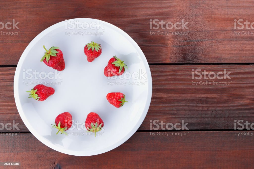 Strawberries on a white plate top view, red berries on a wooden background, fresh strawberries on dark wooden boards, vegetarian food, copy space stock photo