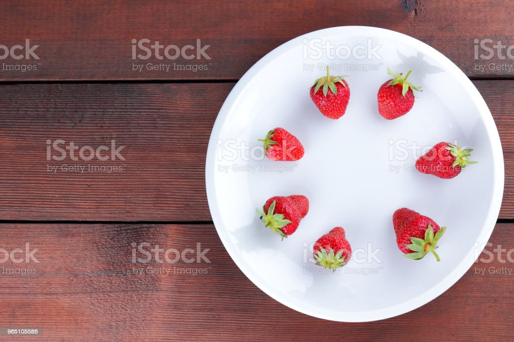 Strawberries on a white plate top view, red berries on a wooden background, fresh strawberries on dark wooden boards, vegetarian food zbiór zdjęć royalty-free
